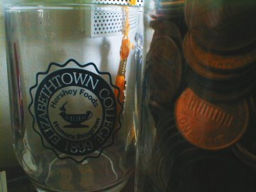 Pennies and Nickels in the Elizabethtown College Hershey Foods Honors Mug. Yes. Logo by J. Nathan Matias